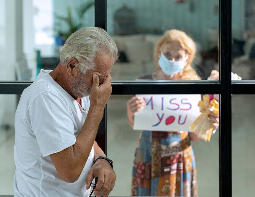 A man is behind a window crying whilst his wife is outside holding a sign saying 'Miss you'.