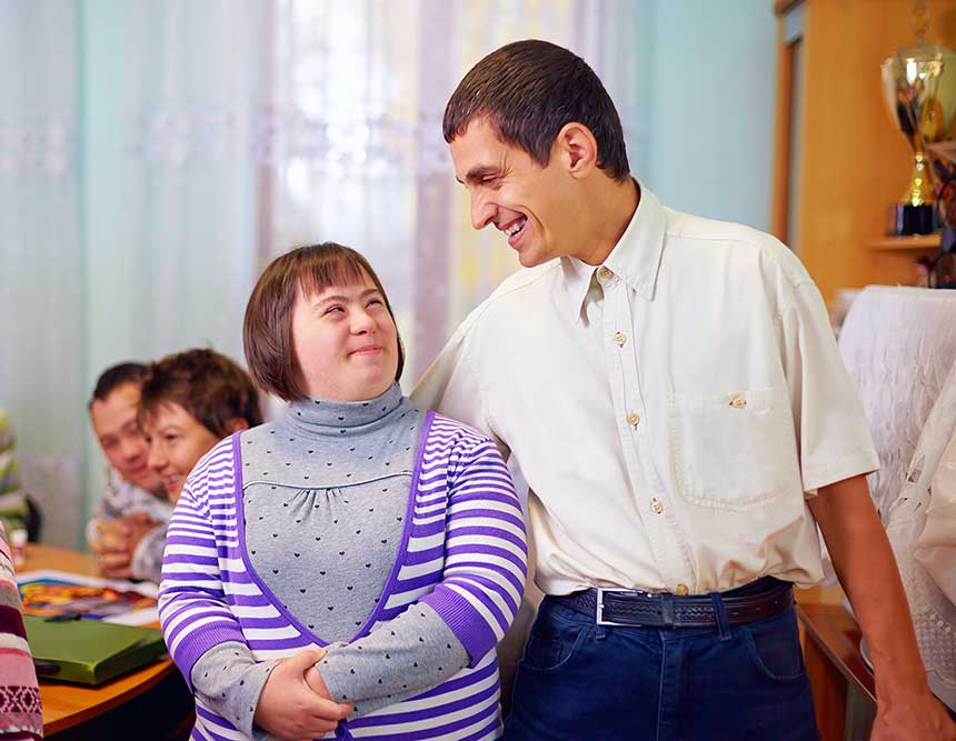 A care provider is standing next to a woman with Down's Syndrome.