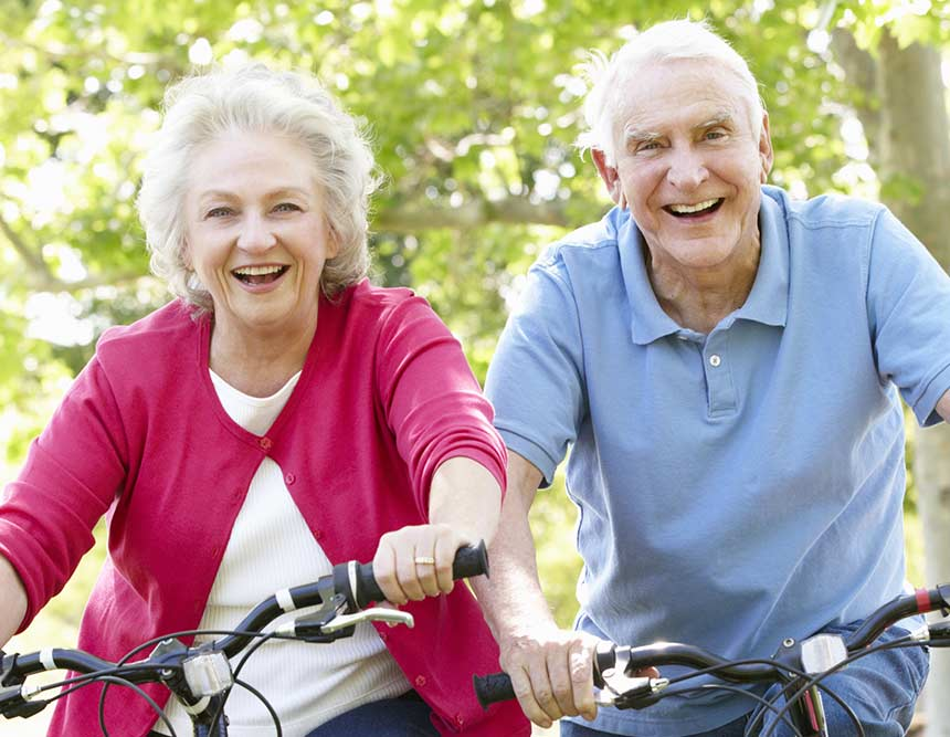 An elderly couple sit smiling whilst on their bicycles. Their young grandchildren also sit on bikes looking happy.