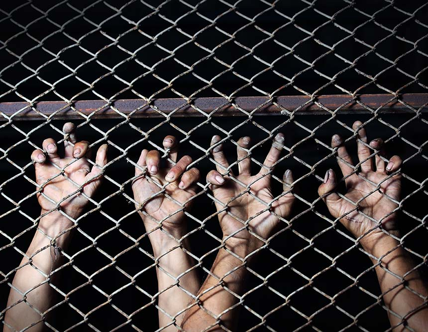 A series of hands clinging onto a chain-link fence.