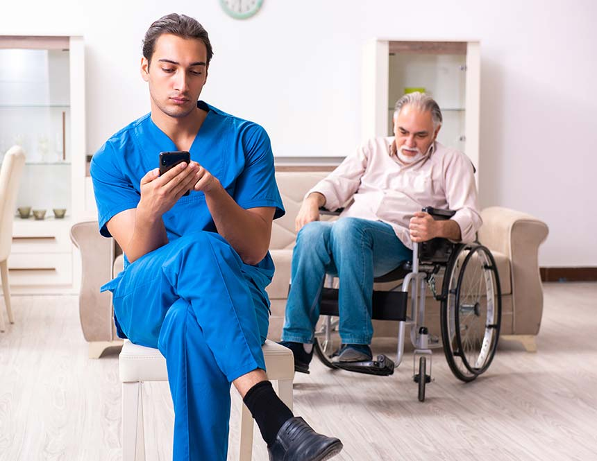 A male nurse sits in a chair using his mobile phone whilst an elderly patient calls out for help.
