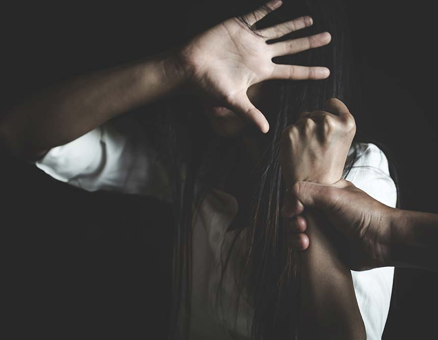 An woman shields herself whilst a man grabs her by the wrist.
