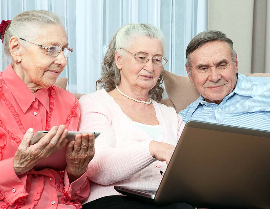 An elderly couple are reading the policy and procedures on a laptop.