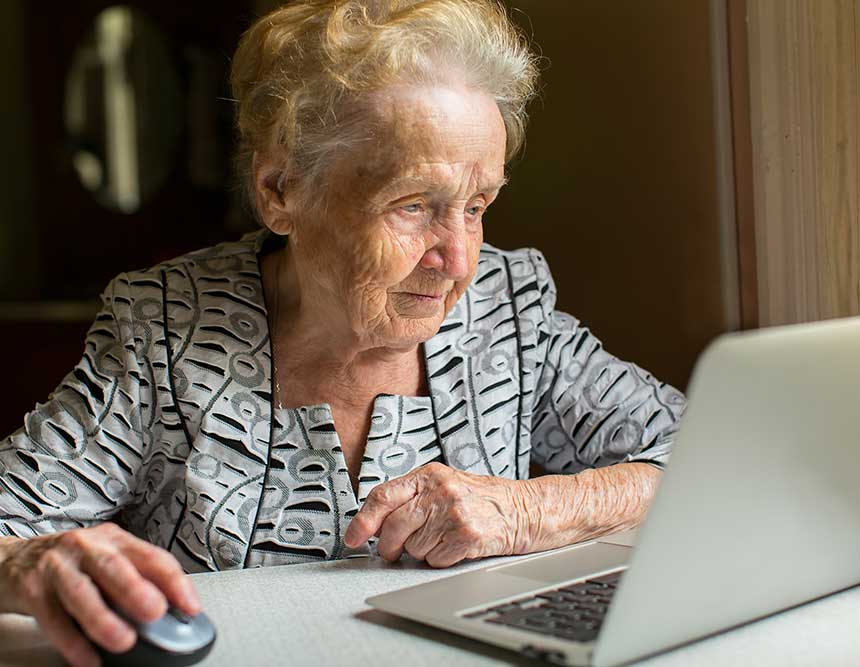 An elderly woman searches for resources on a laptop.