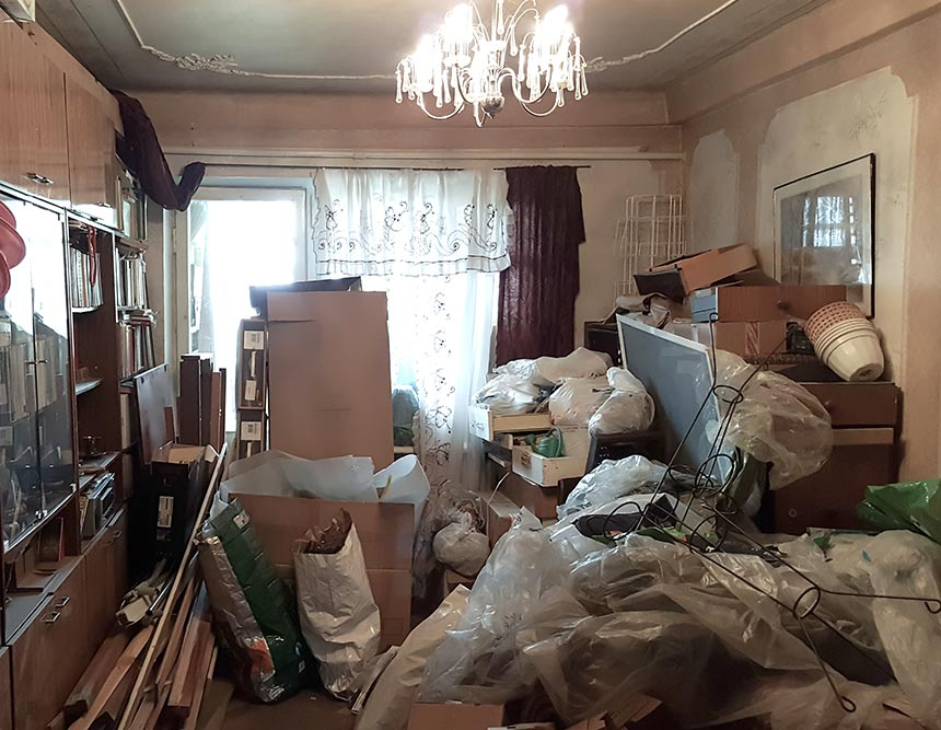 A front-room filled with rubbish, bags and boxes. These are piled up everywhere.