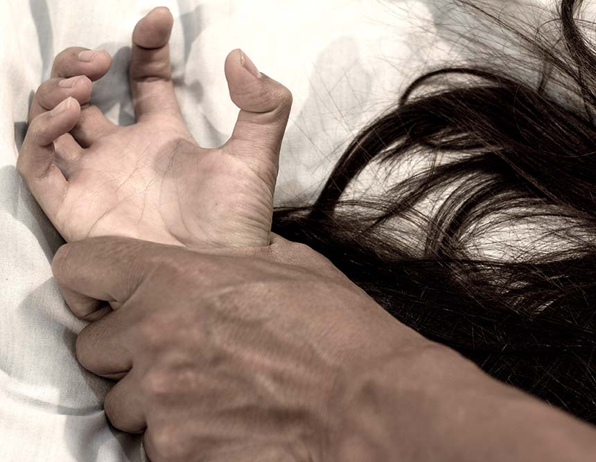 A woman is pinned to a bed by a man. We can see him grabbing her by the wrist.