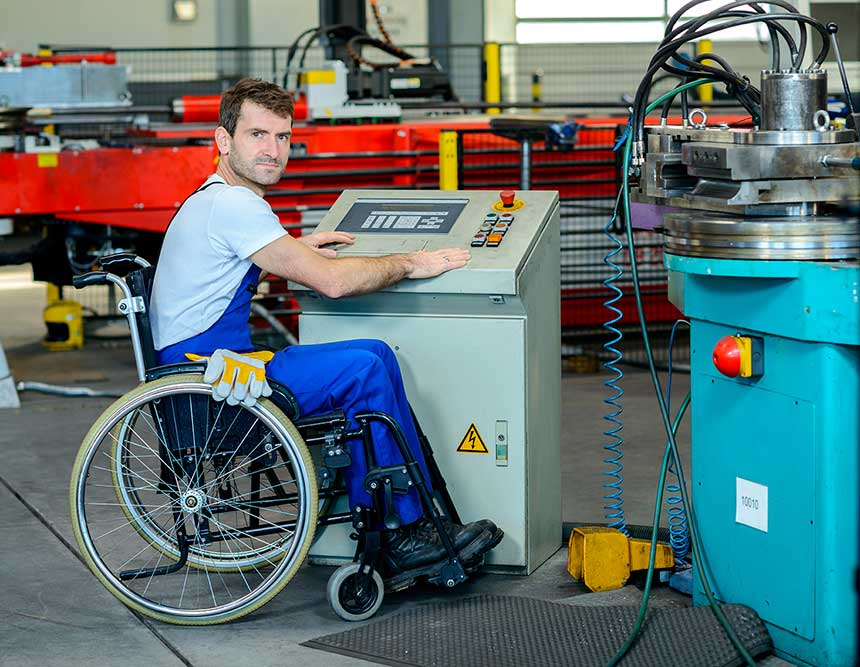 A man in a wheel chair is wearing protective clothing and is operating an industrial machine.