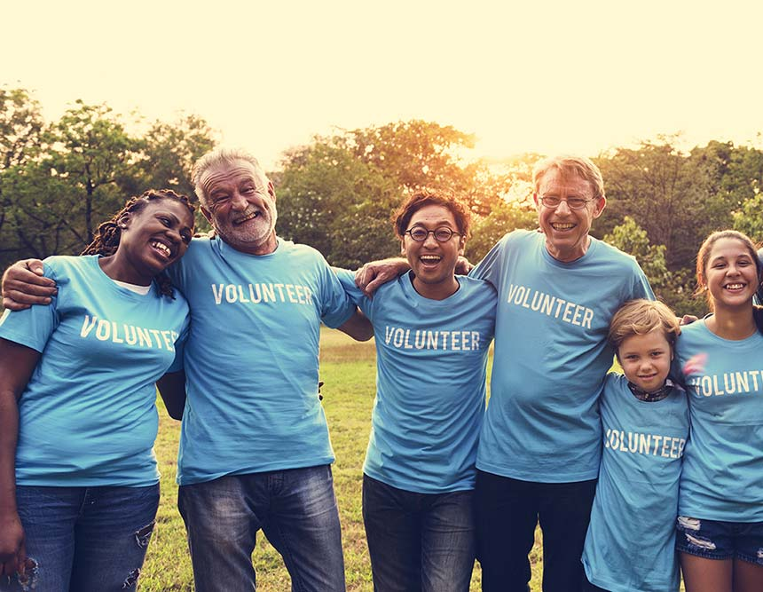 Two ladies and an elderly man wearing blue t-shirts with the word 'Volunteer' in white printed on the front of them.
